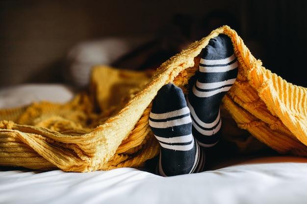 Position confortable du pied dans des chaussettes chaudes sous les couvertures sur le lit