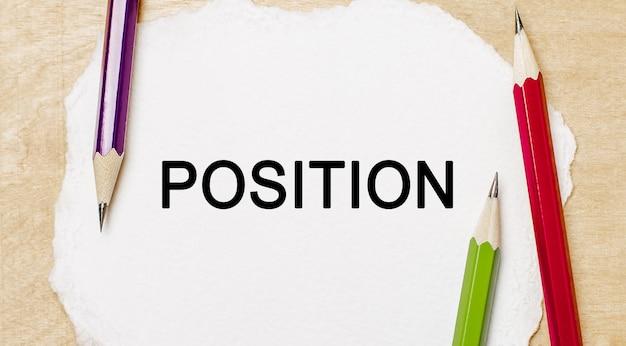Position du texte sur un bloc-notes blanc avec des crayons sur un espace en bois