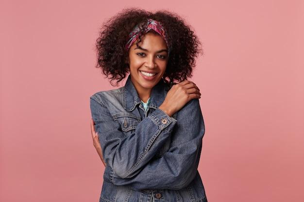 Positive attrayante jeune femme brune à la peau sombre avec une coiffure décontractée se serrant dans ses bras et à la recherche d'un sourire charmant