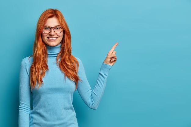 Positive belle rousse à la femme de race blanche avec des points de sourire à pleines dents sur l'espace de copie dans le coin supérieur droit.