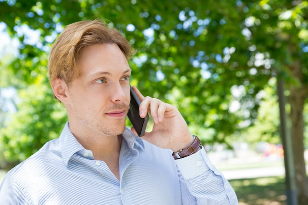 Positive entrepreneur calme appelant sur téléphone mobile