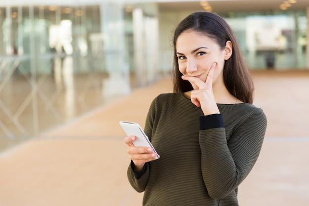 Positive femme latine timide avec téléphone portable touchant le visage