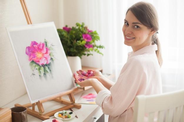 Positive jeune belle fille souriante artiste travaille en studio sélectionne les couleurs du lit pour travailler avec fleur d'églantier rose assis à table avec un chevalet et un bouquet. la créativité conceptuelle comme profession