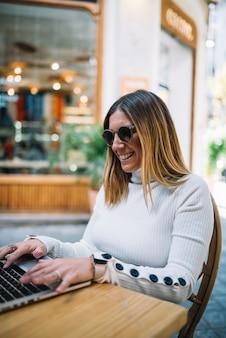 Positive jeune femme à l'aide d'un ordinateur portable à la table dans le café de rue