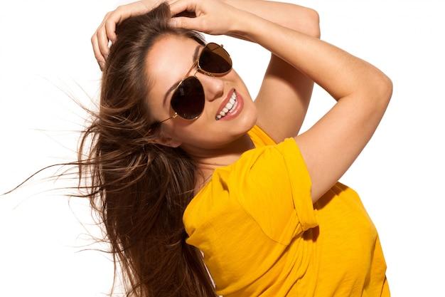 Positive jeune femme à lunettes de soleil