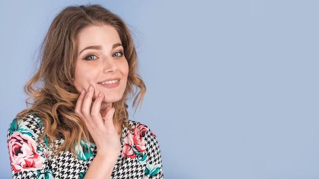 Positive jeune femme en robe élégante avec la main sur la joue