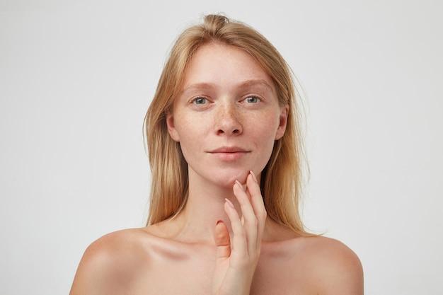 Positive jeune femme rousse attrayante avec une coiffure décontractée touchant son menton avec la main levée et regardant doucement, debout contre le mur blanc