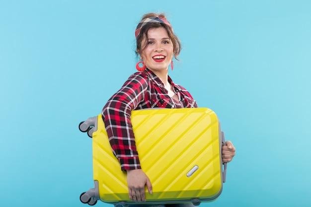 Positive jeune femme souriante dans une chemise à carreaux tenant une valise jaune posant sur une surface bleue