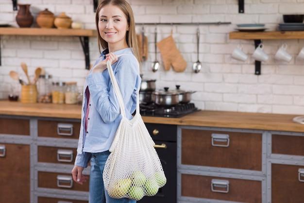 Positive jeune femme tenant un sac écologique avec des fruits biologiques