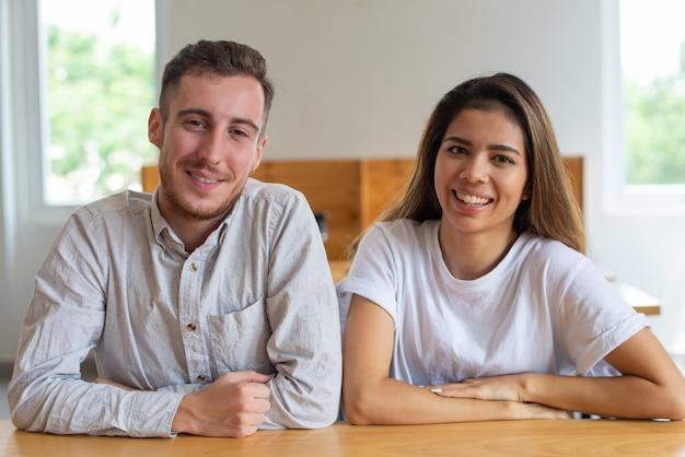 Positive jeune homme et femme assise à la table et posant