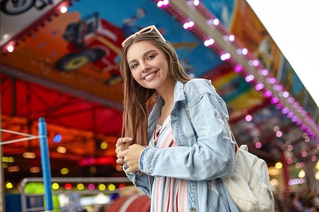 Positive jeune jolie femme aux longs cheveux bruns à la recherche avec un large sourire sincère, portant un sac à dos blanc, un manteau de jeans à la mode et une robe d'été légère