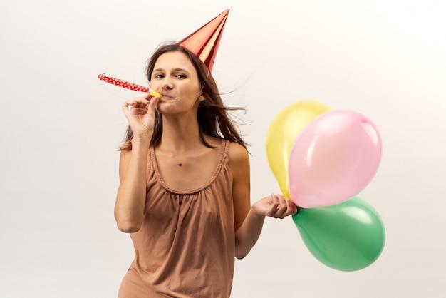 Positive joyeuse jeune fille dans un chapeau de fête et avec trompette et ballons pose pour un portrait aux cheveux longs qui coule. portrait en studio sur fond blanc isolé. vacances, anniversaire, réalisation.