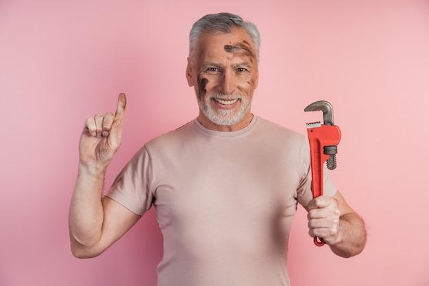 Positive, senior man avec des cheveux gris et une barbe tient un outil dans sa main et a levé son index vers le haut