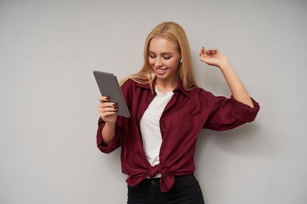 Positive souriante jeune femme séduisante aux cheveux longs, écouter de la musique sur son tablet pc et danser joyeusement avec les mains levées, portant une chemise bordeaux et un t-shirt blanc sur fond gris clair
