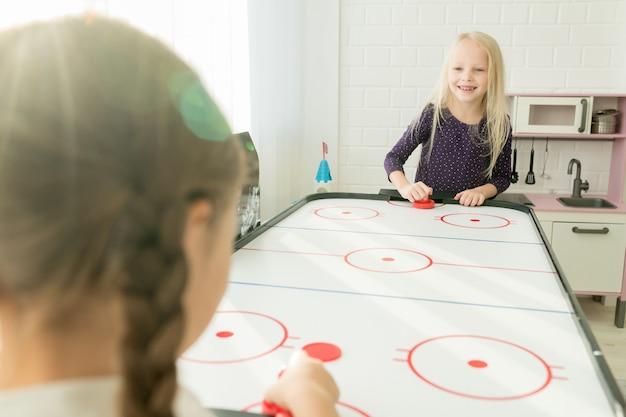 Positives petites filles s'amusant dans la salle de jeux