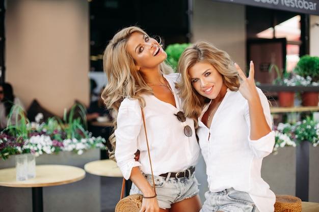 Positivité et jolies femmes posant en plein air près d'un café et montrant la paix