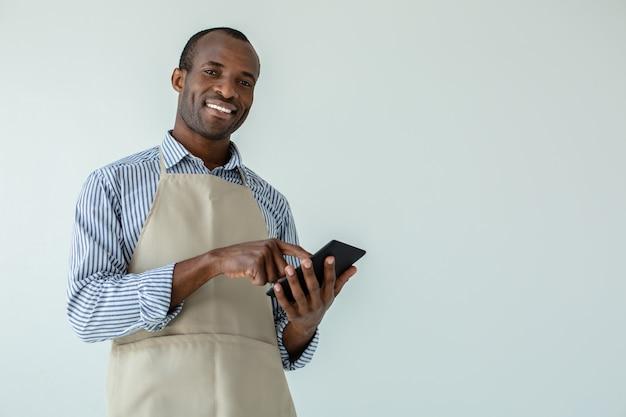 Positve beau serveur afro-américain recevant une commande contre le mur blanc