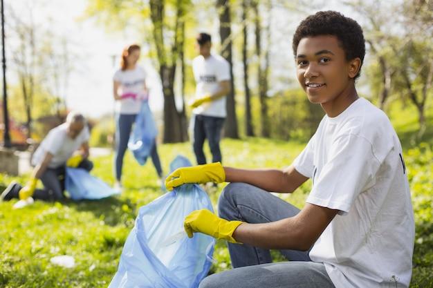 Les possibilités de bénévolat. homme bénévole attrayant à l'aide d'un sac poubelle tout en regardant la caméra