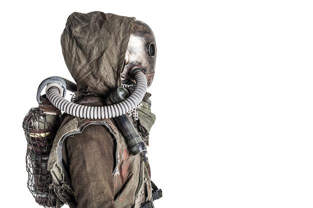 Post-apocalyptique effrayant, vivant sous terre, créature avec une lanterne vintage sur l'épaule, portant des chiffons et un masque à gaz effrayant sous un capot en lambeaux, tournage en studio isolé sur blanc avec espace de copie
