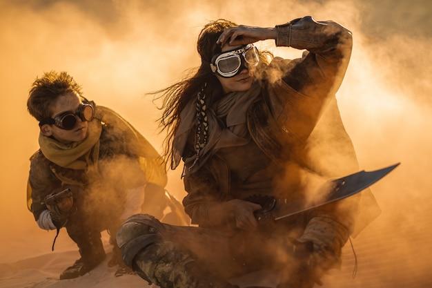 Post femme apocalyptique et garçon à l'extérieur dans un désert
