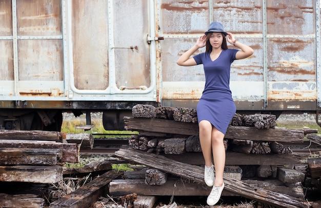 Poste de dame asiatique sur vieux train de cassage dans le concept d'aventure