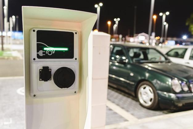 Poste publique chargeur de véhicules électriques placés dans le parking d'un supermarché.
