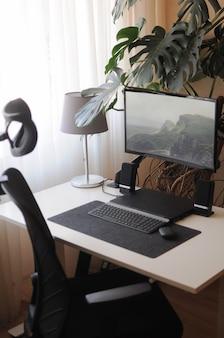 Poste de travail à domicile avec écran incurvé et chaise orthopédique. intérieur à l'intérieur avec des plantes