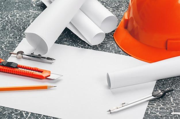 Poste de travail d'ingénieur avec plans, boussole, crayon et casque de sécurité