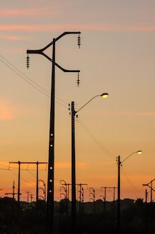 Postes électrisants avec fond de ciel coucher de soleil orange.