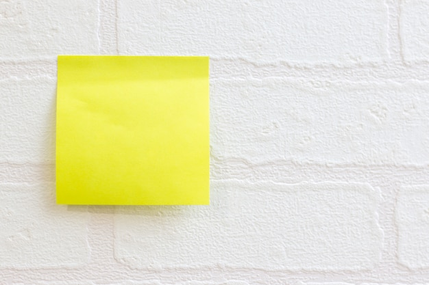 Postez-y une note ou un post-it sur le motif de briques de papier peint blanc utilisé pour