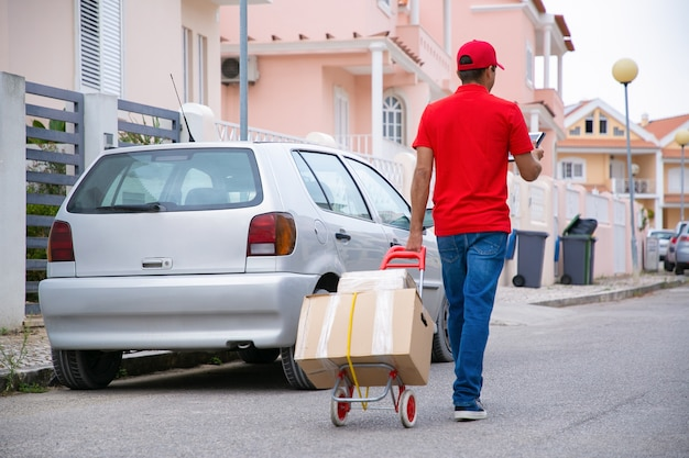 Postman holding tablette et chariot à roulettes avec boîtes en carton. courrier professionnel caucasien en uniforme rouge marchant dans la rue avec des colis en carton sur le chariot. service de livraison et concept de poste