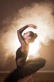 Posture de ballet vue de côté en fumée