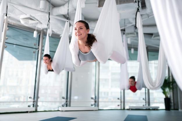 Posture de yoga aérien. femme séduisante aux cheveux noirs se sentant satisfaite après une pose de yoga aérienne réussie