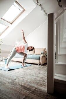 Posture de yoga. femme qui travaille dur pliant sa taille pendant une session sportive en se tenant debout sur un tapis bleu