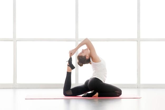 Posture de yoga à une patte de pigeon royal. eka pä da. rä jakapotä sana. prise de vue en studio