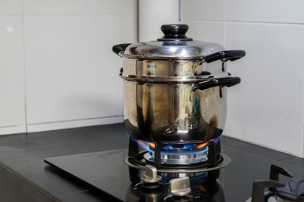 Un pot en acier inoxydable est placé sur une cuisinière à gaz.