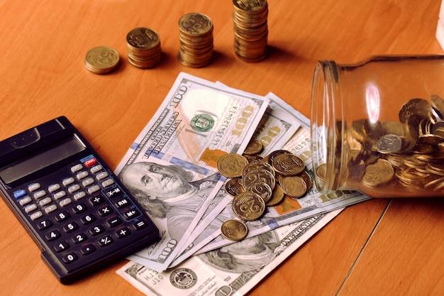 Pot avec de l'argent tombant des pièces pour dollars, calculatrice sur la croissance d'arrière-plan du concept de pièces floues