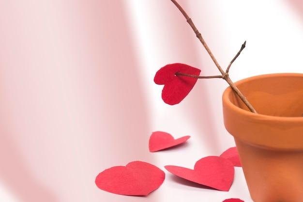 Pot en argile avec branche d'arbre et coeurs rouges autour du pot