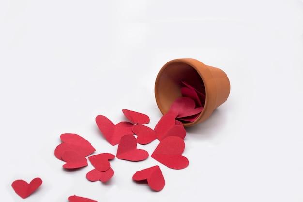 Pot en argile et coeurs rouges autour du pot sur fond blanc