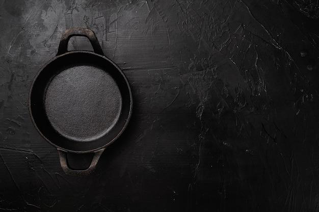 Pot en argile vide noir avec espace de copie pour le texte ou la nourriture avec espace de copie pour le texte ou la nourriture, vue de dessus à plat, sur fond de table en pierre noire noire