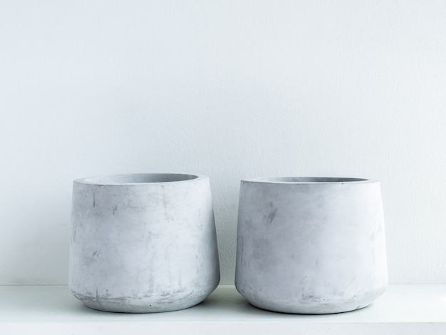 Pot en béton. deux jardinières de ciment géométriques modernes vides sur étagère en bois blanc sur blanc
