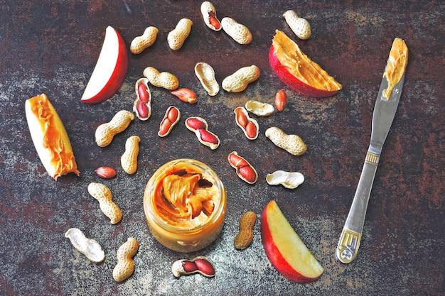Pot de beurre d'arachide, cacahuètes en pelure, tranches de pomme et couteau. pommes au beurre d'arachide sur une table authentique et élégante.