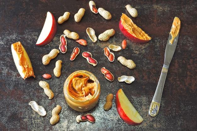 Pot de beurre d'arachide, cacahuètes en pelure, tranches de pomme et couteau