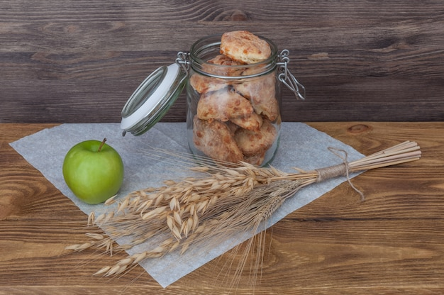 Un pot avec des biscuits faits maison et une pomme sur un fond de planches de bois.
