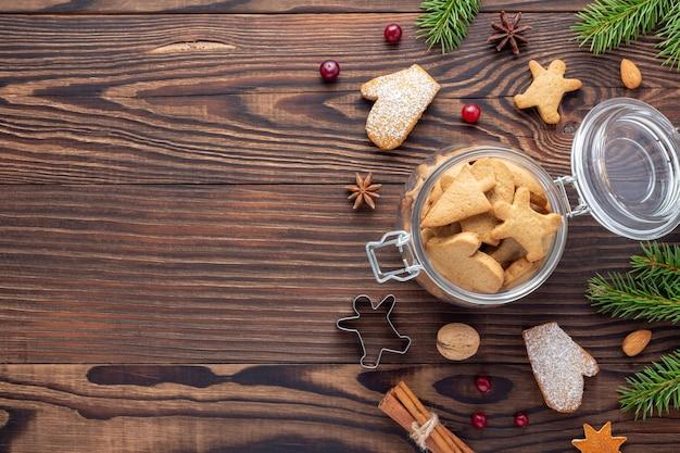 Pot avec des biscuits parmi les ingrédients pour la boulangerie de vacances sur la table en bois