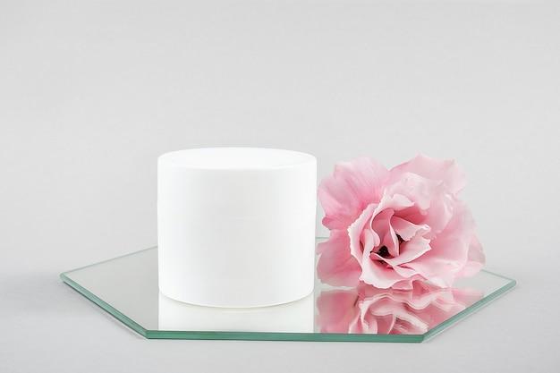 Pot blanc cosmétique blanc et fleur rose sur miroir, fond gris. maquette de concept de beauté cosmétique de spa biologique naturel, vue de face.