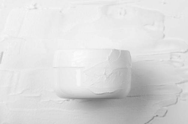 Pot blanc fermé souillé de crème pour le visage blanc sur fond de crème enduite