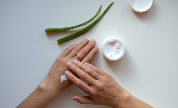 Pot blanc de mains de femme avec de la crème et des feuilles d'aloès sur fond blanc