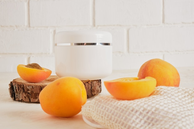 Pot blanc en plastique d'abricots pour la crème ou les cosmétiques sur un podium en bois à partir d'un bois coupé à la scie sur fond clair