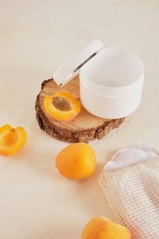 Pot blanc en plastique d'abricots pour la crème ou les cosmétiques sur un podium en bois d'une scie coupée d'un arbre sur un fond clair, contre un mur de briques blanches